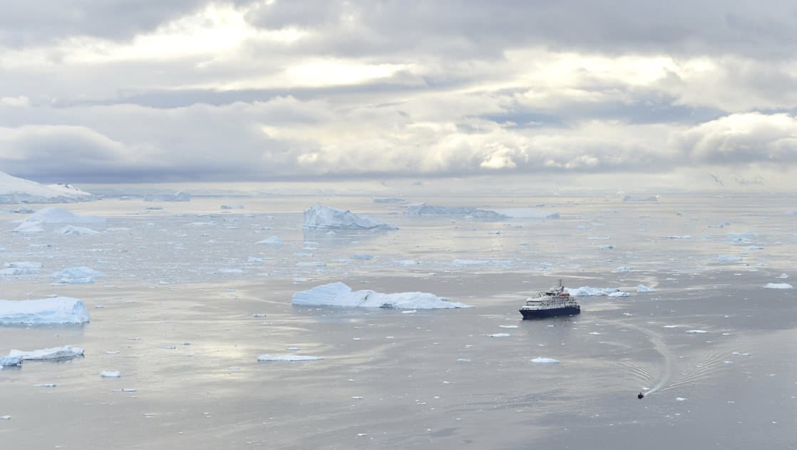 looking down at an antarctica expedition ship on calm water with icebergs floating around it on a cloudy day