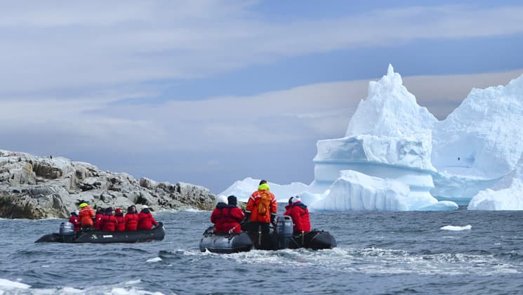 adventure travelers in red jackets travel in two zodiac rafts toward an iceberg during an overcast day in antarctica