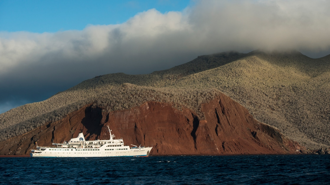 The all white Galapagos small ship the Legend floats in the dark blue ocean against a deep red hillside of Rabida island.