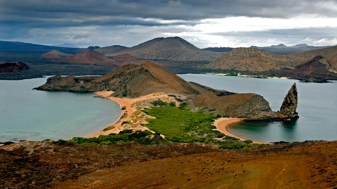 an aerial view of galapagos bay with rocks jutting out of water, green hillsides, and empty pristine beaches