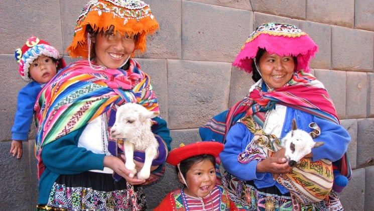 two women in colorful local clothing with two goats and two children in peru