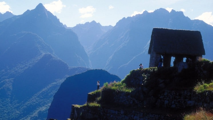 cliffside stone hut surrounded by the mountains of peru seen on machu picchu explorer land tour