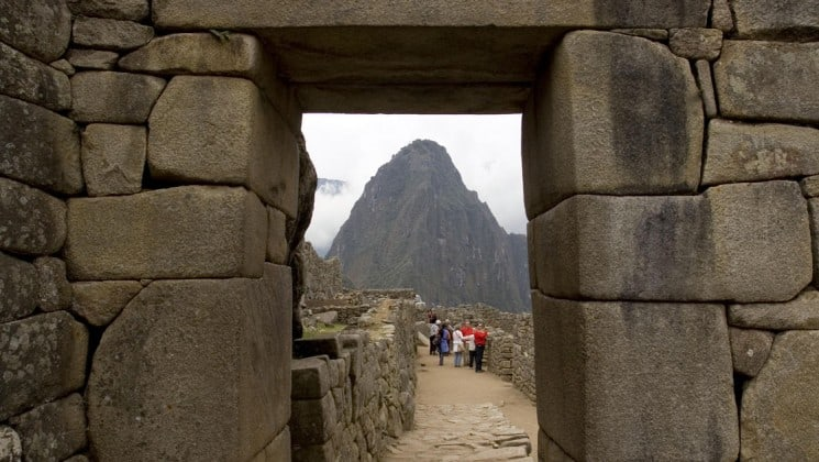 travelers explore machu picchu with mountains in background