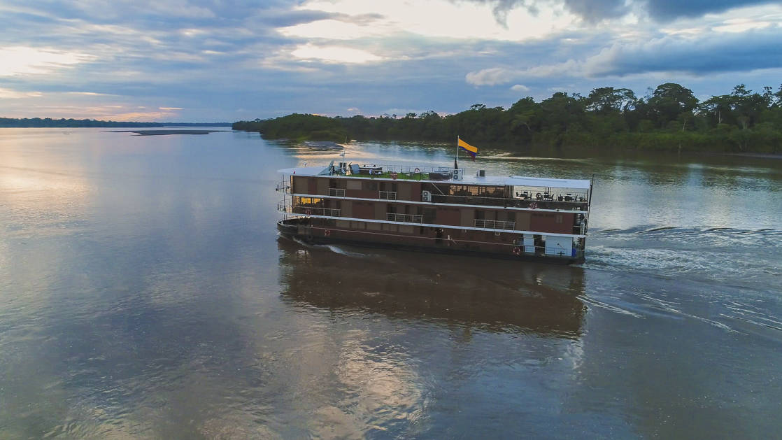 the small ship manatee cruising down a river in the amazon as the sun is going down