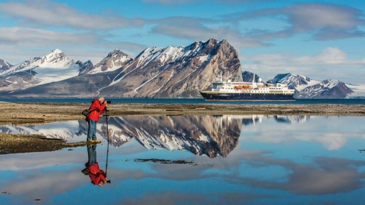 photographer, mountains, arctic waters, port side of small cruise ship