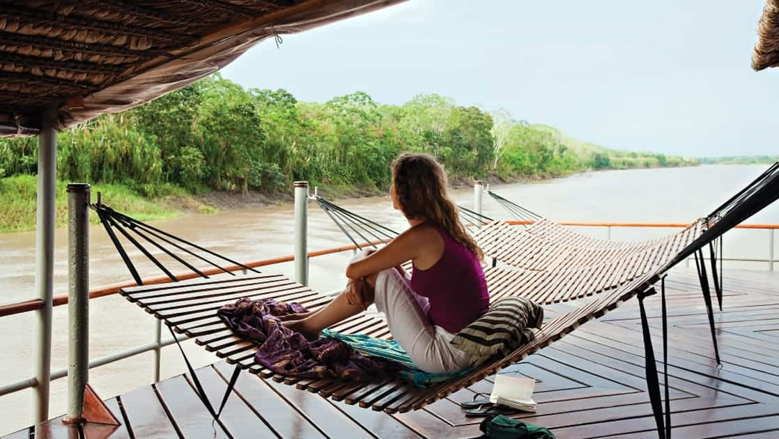 Woman lounging in a hammock on the top deck the Delfin II in the Amazon.