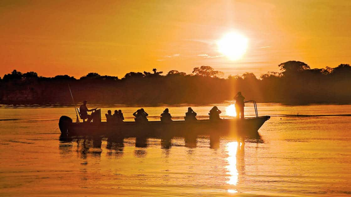 Canoe with people looking for wildlife on the river in the Amazon during an orange sunset aboard the Delfin II in the Amazon