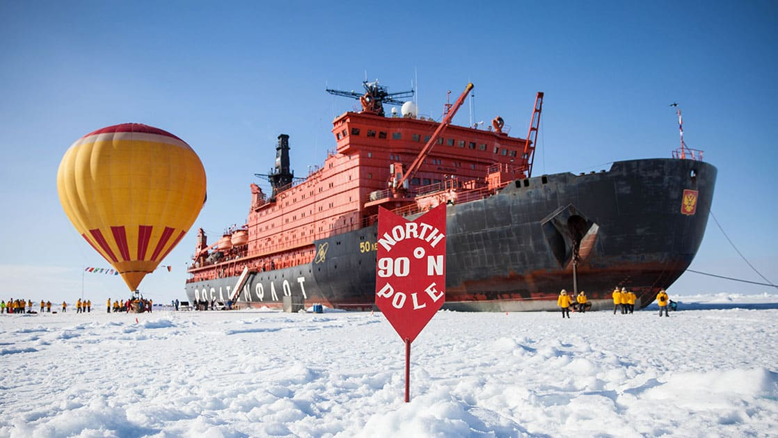 parked on the ice behind a red arrow marking the true north pole the large 50 years of victory ship sits, next to it a yellow and orage hot hair balloon is inflated