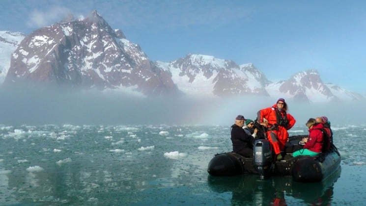 zodiac in icy arctic waters in north spitsbergen greenland