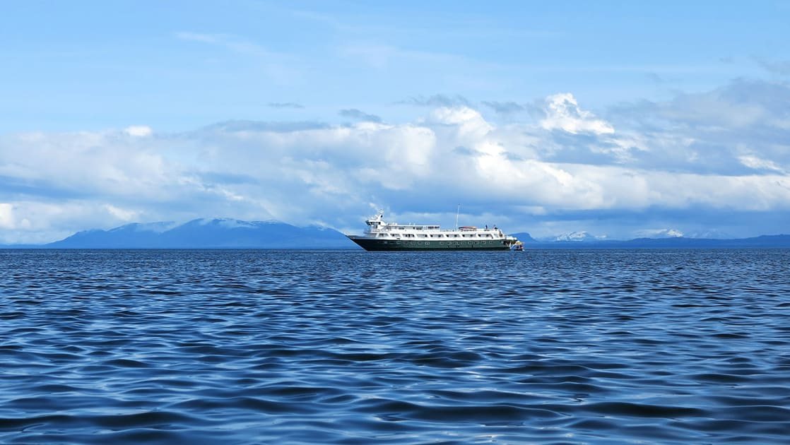 The Wilderness Discoverer small Alaska ship sails along the horizon line of the ocean with a blue sky and clouds.