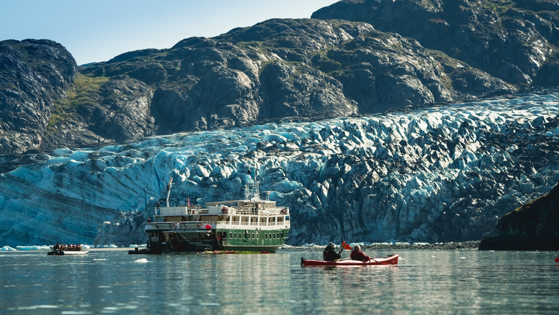 The white and green small ship the Wilderness Adventurer floats in front of a massive glacier in Alaska as kayakers paddle around it.