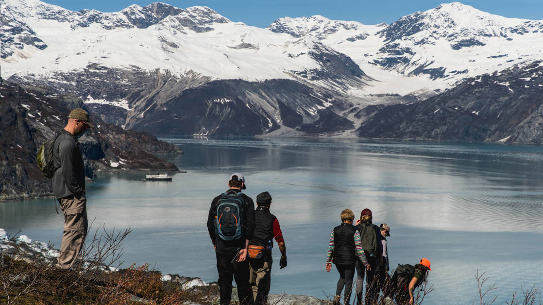 Guests Hiking Lamplugh in Glacier Bay witha view of a fjord with a glacier.
