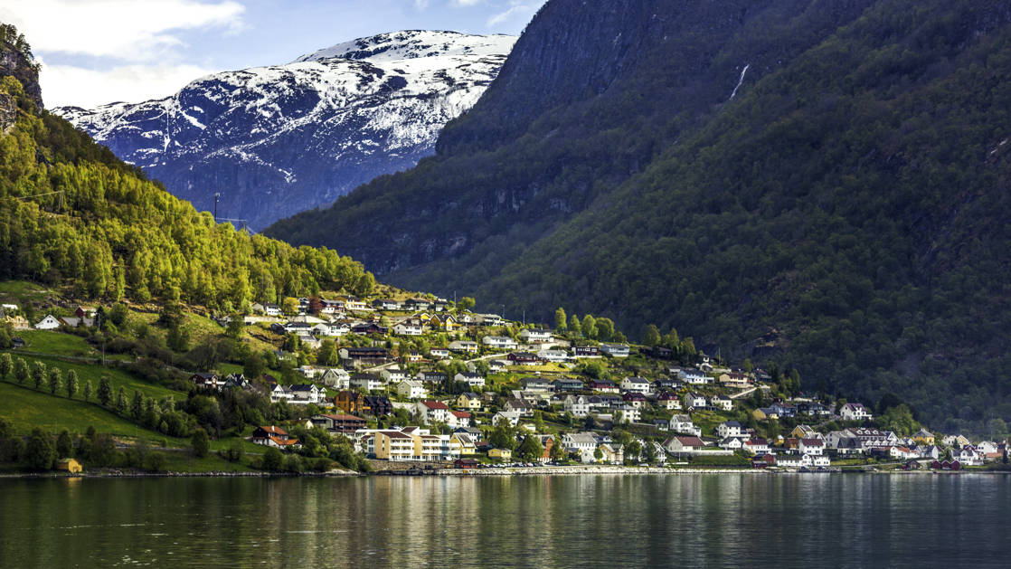 The village of Flam in valley between the fjords of Norway with a snowy mountain in the distance