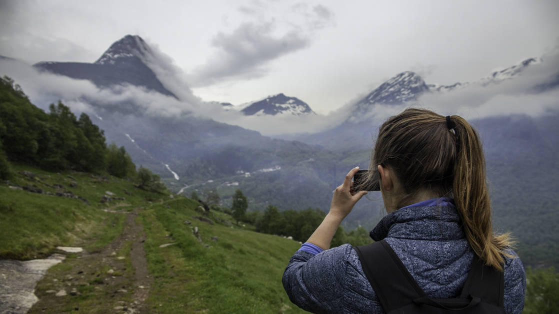 Woman taking a picture while on a hiking trail in Geiranger Fjord in Norway