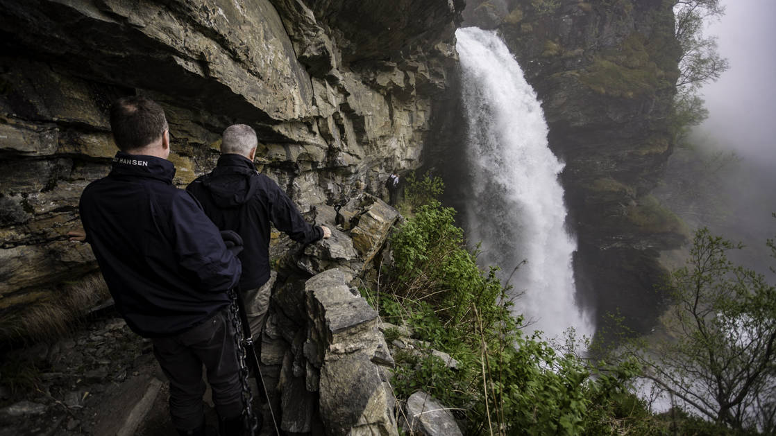 Two people hiking next to a waterfall in Geiranger Fjord in Norway