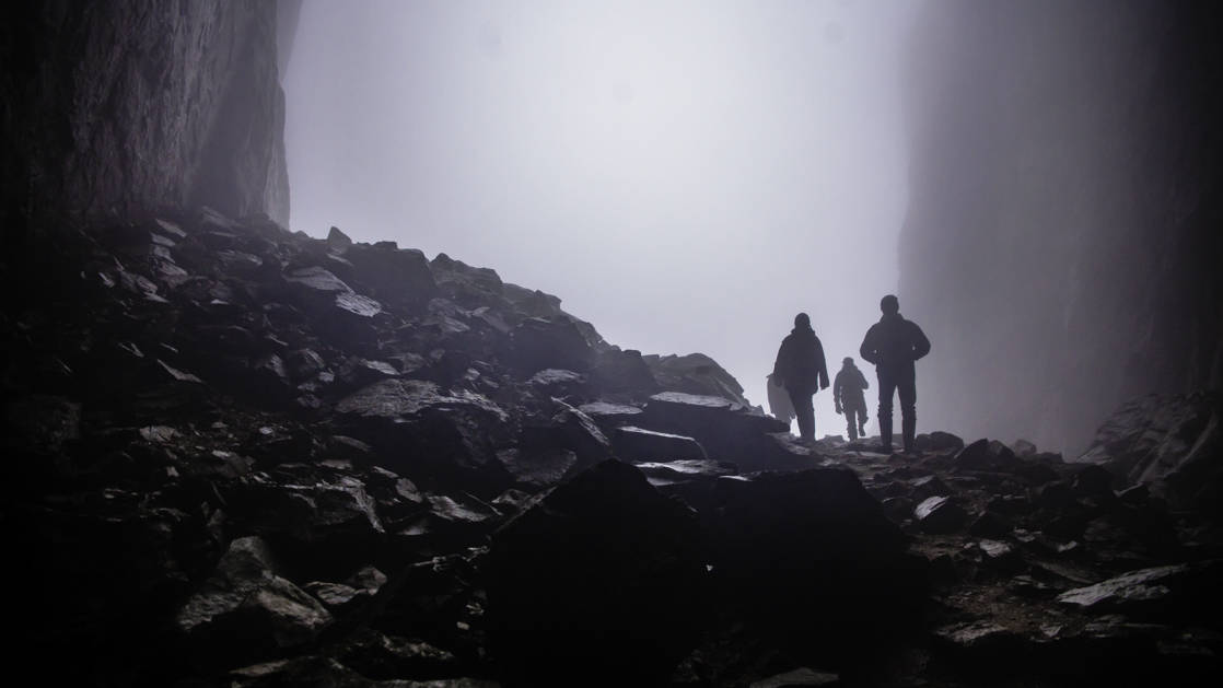 The silhouette of three people hiking in the misty Torghatten granite mountain on the island of Torget in Norway