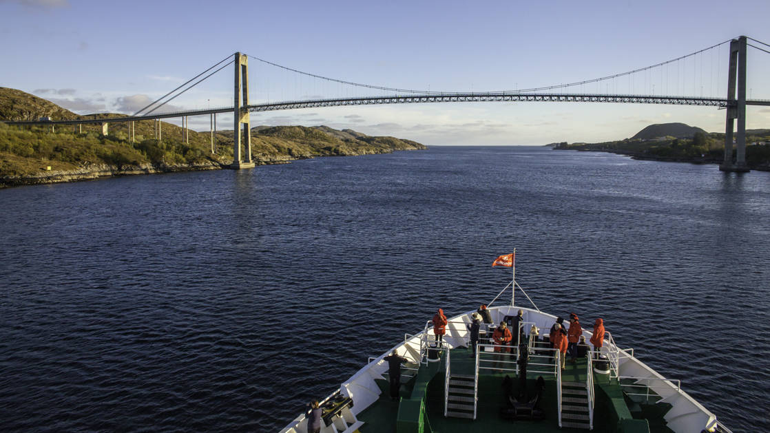 Bow of the small expedition ship cruising in Torghatten and about to go under a bridge