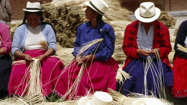 local women wearing panama hats weave straw on otavalo escape ecuador land tour