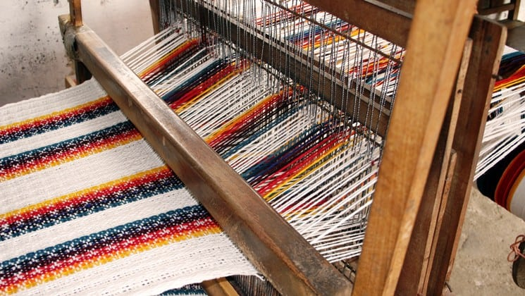 large tapestry being woven on loom on otavalo escape ecuador land tour