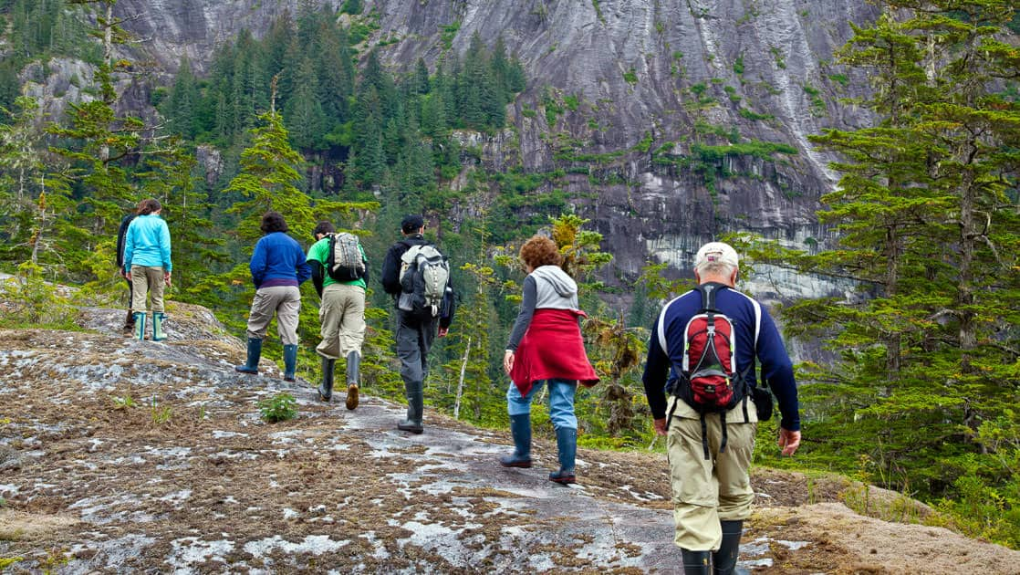 line of adventure travelers on an alaska hiking excursion along a ridge as an activity offered from their small ship cruise