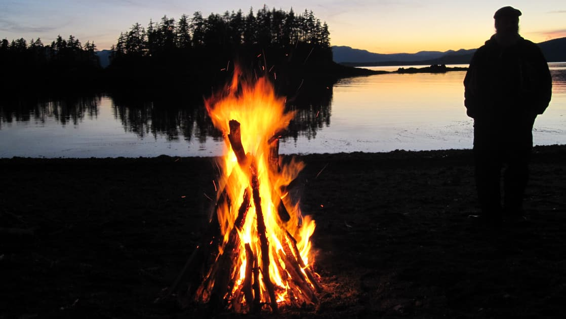 silhouette of an adventure traveler looking out at the eastern passage in alaska while a bonfire burns in the foreground
