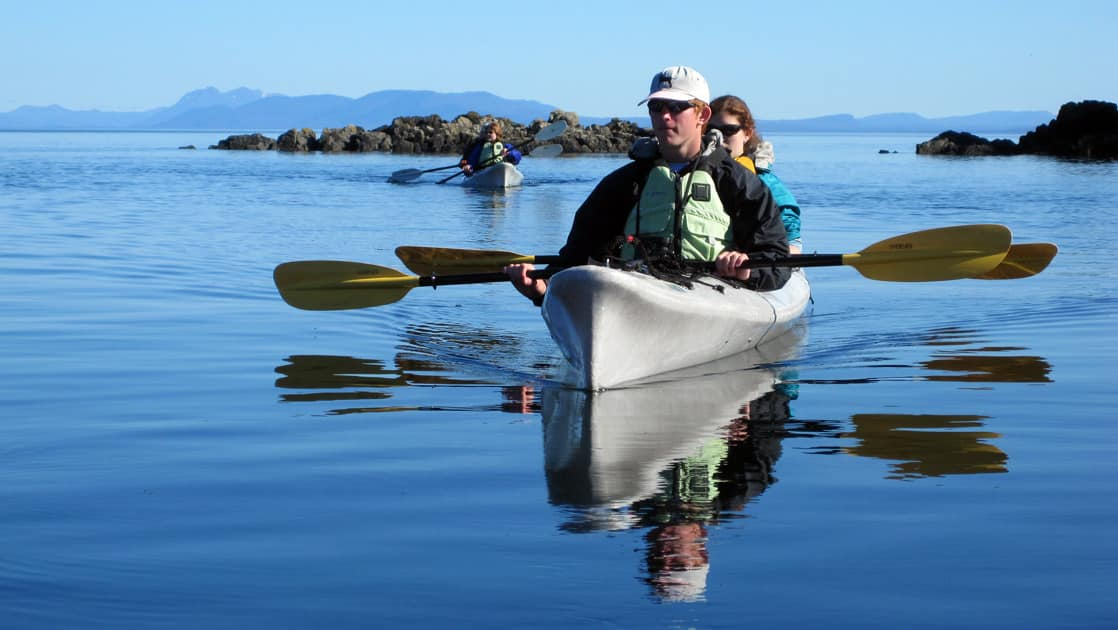 adventure travelers sit in kayaks on a calm sunny day in the eastern passage of alaska