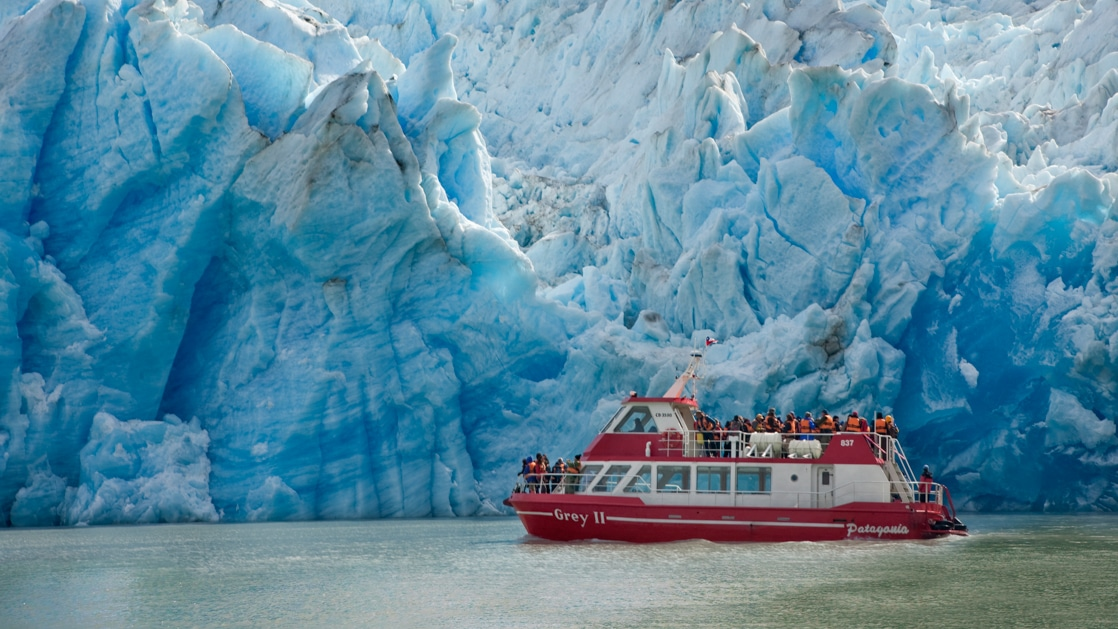 Red & white boat cruises beside a massive blue glacier in Torres del Paine National Park, Patagonia, Chile.