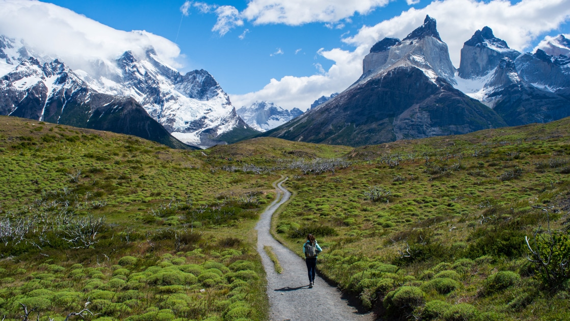 Traveler walks down an empty gravel road with bright green grassy fields on either side, heading toward massive snow-covered peaks.
