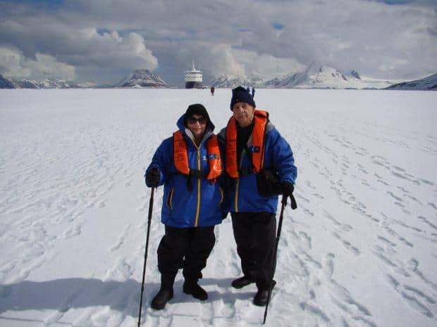 Two people on the snow in Antarctica with their walking sticks and small ship far in the background.