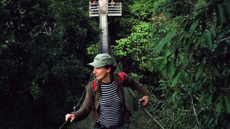 female solo traveler walking through the amazon jungle canopy on a land tour