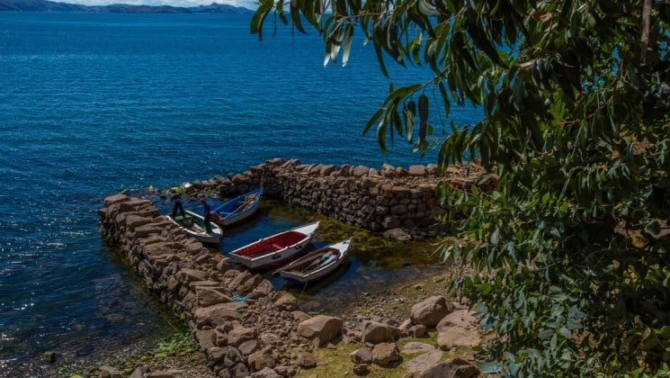 four small boats docked at a stone pier on peru highlights land tour