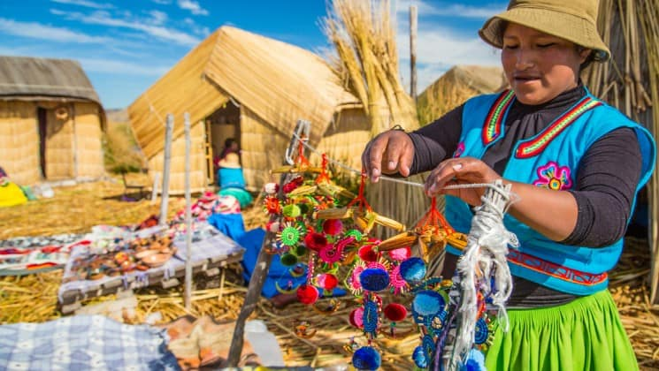 peruvian woman in colorful clothing hangs crafts at market on peru highlights trip