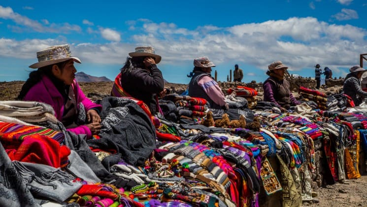 colorful blankets and clothing for sale from local artisans at market on peru highlights land tour