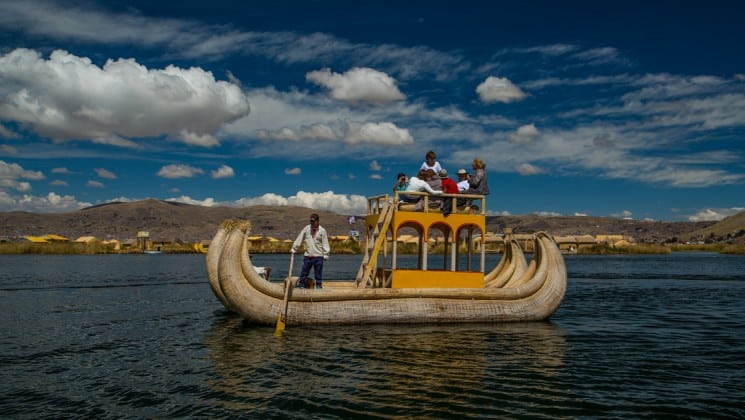 family poses for photo on double-decker boat on peru highlights land tour