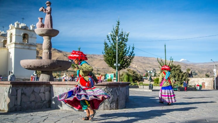 woman in traditional peruvian clothing dances by fountain on stone streets on peru highlights trip