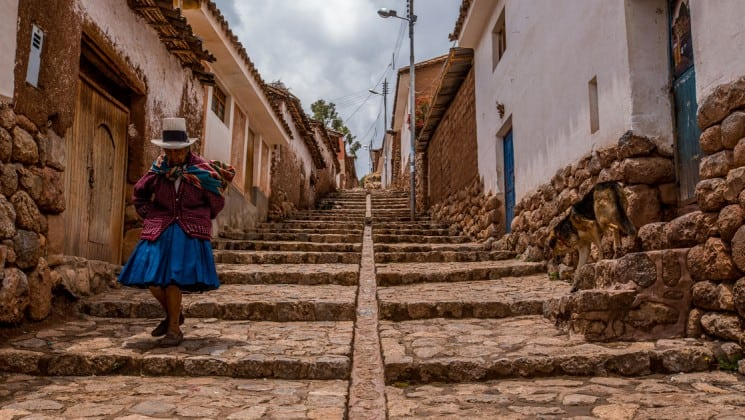older woman descending cobblestone steps on peru highlights trip