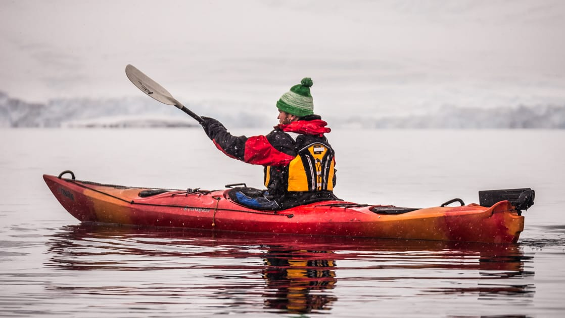 Solo Kayaker in water paddling towards the snowy peninsula in the polar circle.