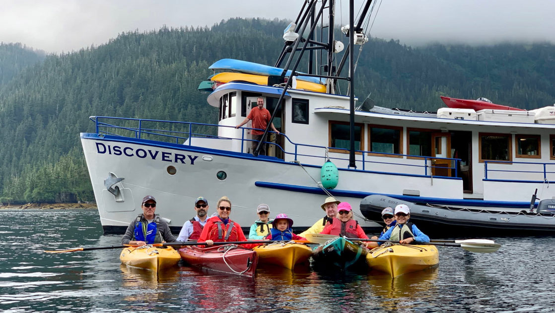 Family of kayakers sits in yellow boats in the water with Alaska small ship Discovery behind, on a cloudy day.