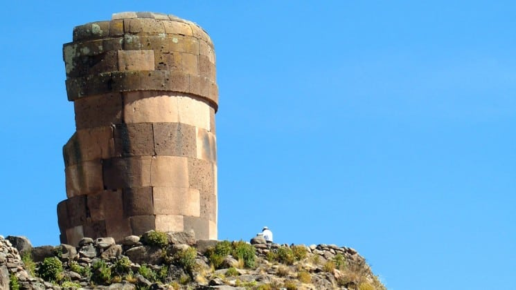 man sits on cliff near ruins of tower above lake titicaca in peru