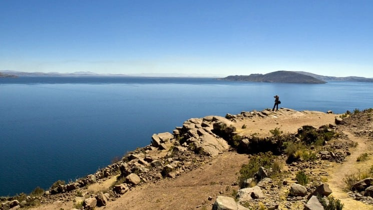 wide view of lake titicaca and photographer on peru land tour