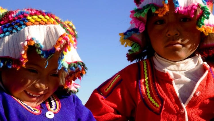 two local children in colorful hats on puno & lake titicaca land tour in peru