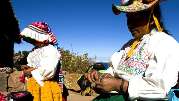 local craftswomen in colorful clothing make goods to sell at market near lake titicaca