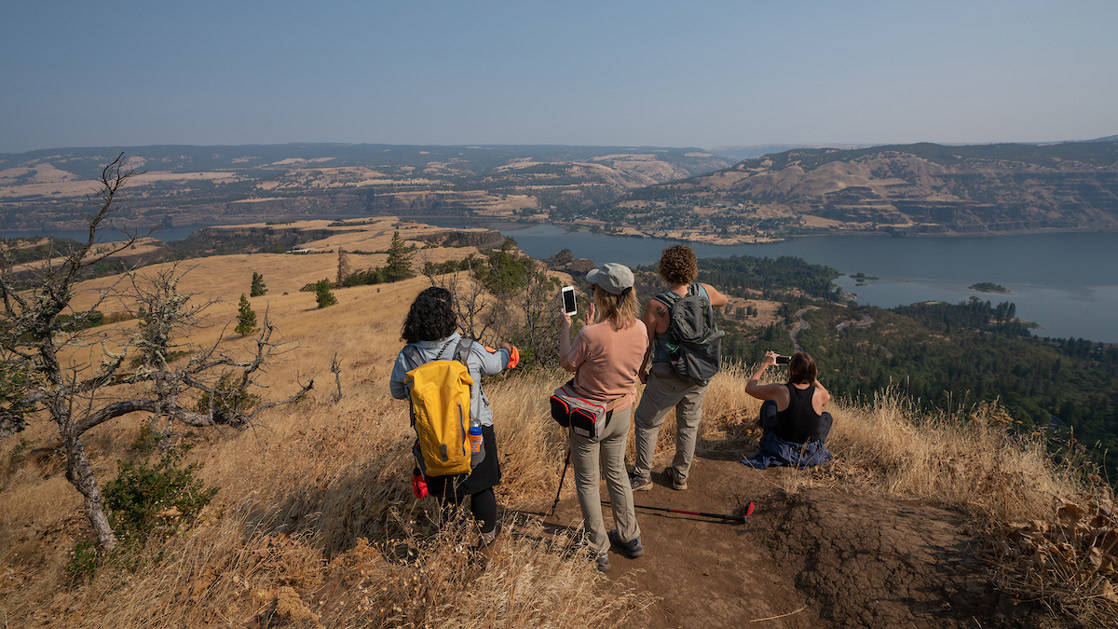 A group of hikers take photos of the sweeping view at the top of Rowena Crest on the Rivers of Adventure cruise