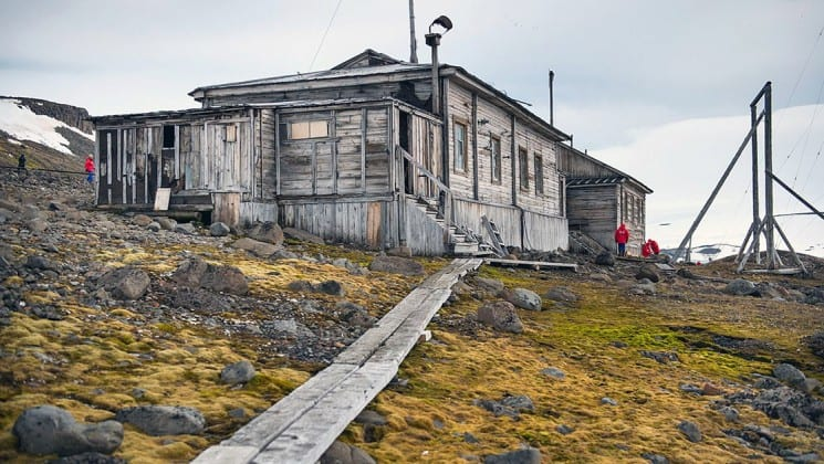 A clapboard building on a grassy hillside in franz josef land in the high arctic