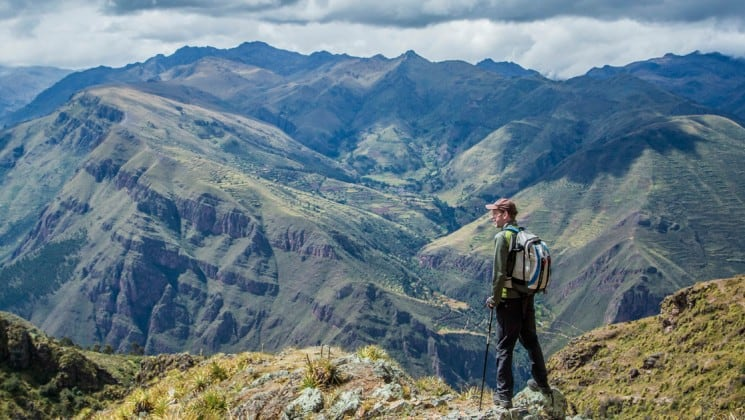 hiker cliffside with epic views of sacred valley on peru land tour