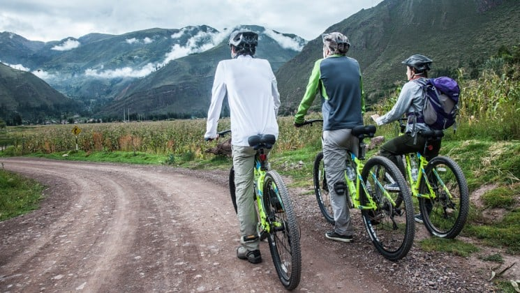 three mountain bikers on rural road with snow-capped mountains ahead on peru land tour