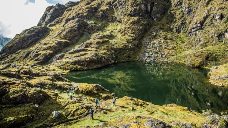 trekkers approach a mountain pond on sacred valley & lares adventure to machu picchu