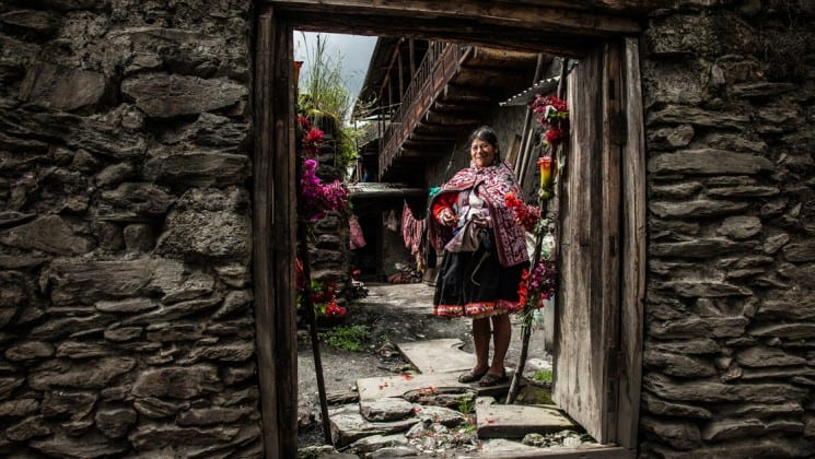 local peruvian woman seen through stone doorway on sacred valley & lares adventure to machu picchu