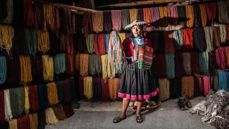 local peruvian woman showing samples in textile shop on sacred valley & lares adventure to machu picchu