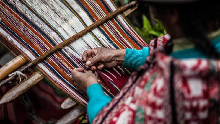 closeup of hands of woman weaving on sacred valley & lares adventure to machu picchu land tour